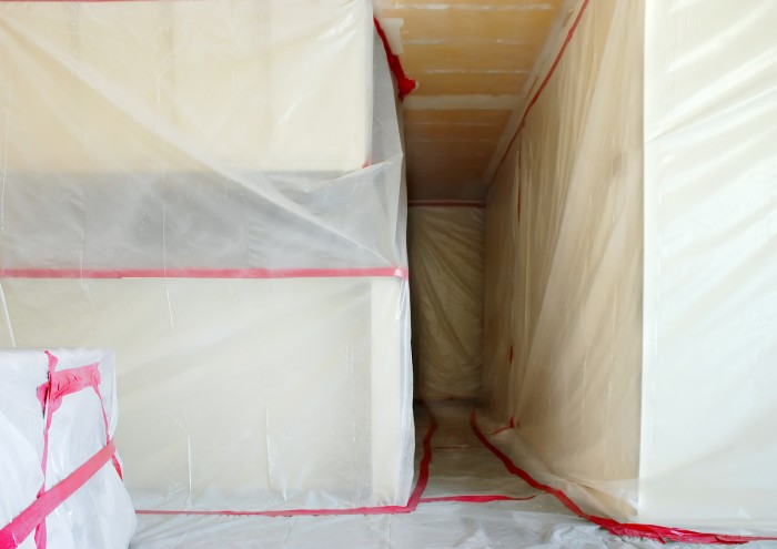 Room covered with clear plastic sheeting after asbestos abatement completed on popcorn ceiling